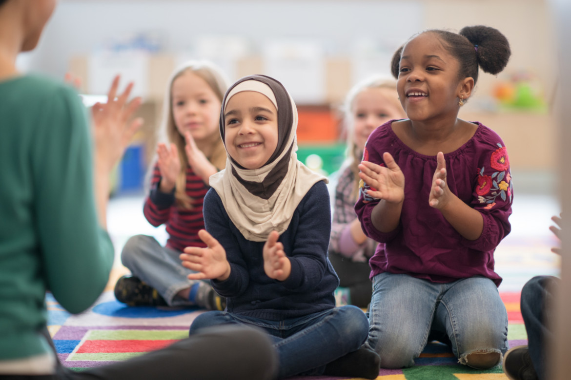Young children in a classroom singing and clapping together.