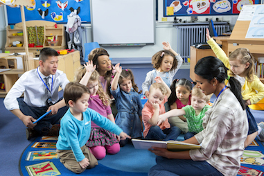 A teacher reading a book aloud as small children sit on the rug listening. Some children have their arms raised. An additional teacher is in the background.